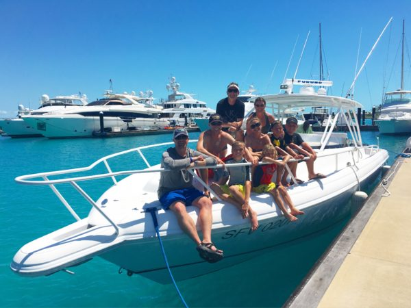 A family poses on the bow of Due West before heading off on a fishing and custom cruise combination boat tour